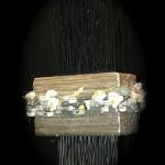 Un pain de mousse oasis de grande dimension décoré de fleurons d'orchidées et de galets oasis est posé sur  un vase noir.