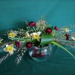 Dans le vase flottent trois renoncules et sur le vase, jonquilles et renoncules soulignent la ligne de branches  de saule.