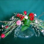 Sur une grosse bulle de verre transparent, jeu de tulipes et renoncules.