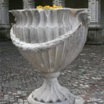 Grand vase medicis dans la cour d'accueil pavée du château.