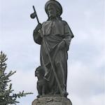St Roch, patron des pèlerins sous le double aspect du pèlerin au large chapeau avec la coquille et du pestiféré secouru par un chien, découvrant son genou pour montrer sa plaie.