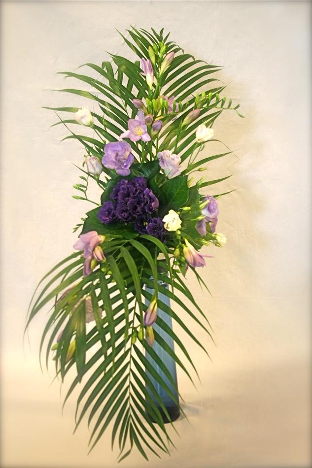 Lisianthius et freesias composent sur une bouteille en verre bleu, un camaïeu de mauves dont les fleurs foncées sont soulignées de feuilles de lierre.