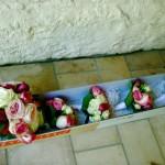 Bouquet rond de grosses roses pour la mariée et bouquets assortis de roses pour les petites filles du cortège.