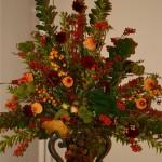 Composition traditionnelle triangulaire de feuillages, baies, fruits sauvages et quelques dahlias.