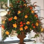 Composition traditionnelle triangulaire de fleurs, feuillages et baies.