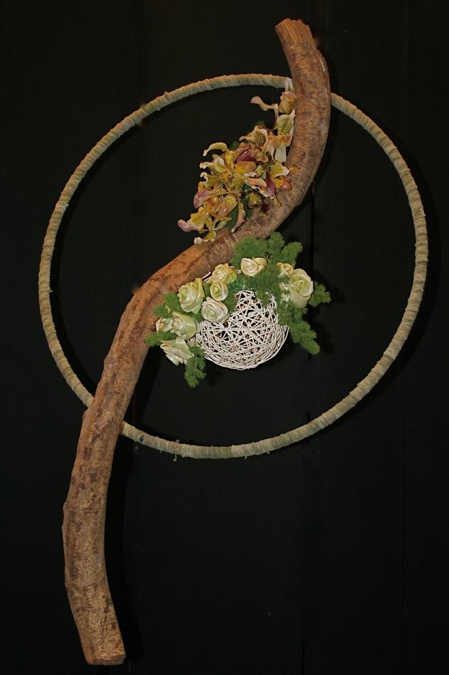 Sur la branche s'équilibrent deux masses de végétaux. En haut, des orchidées Paphiopedilum ou Sabot de venus et en bas, des roses en feuilles de poireaux roulées.