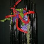 Avec des bambous teints en noir et des  lianes rouges, Madame Lacipieras a choisi des orchidées Vanda du poivre violet et une descente de Tillandsia.