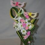 Fantaisie aux couleurs pastel : les trois loups, artistiquement montés sur un fil de fer, sont placés au-dessus du bouquet de chrysanthèmes et petits oeillets rose tendre.