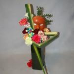 Des gros oeillets et des boules de papier collées en grappes de couleurs vives. Le masque de terre cuite est décoré de petits fruits verts de palmiers.