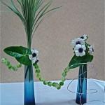 Des choux de Bruxelles enfilés sur du fil à bonsaï animent le duo de bouteilles bleues. Atelier Inspirations Florales.