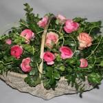Cette vannerie rustique est garnie de roses et de renoncules.