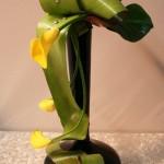 Arums jaunes et feuilles de bromeliacées, vase noir au col allongé.