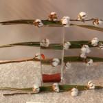 Sur un vase transparent : des lignes en fleurs de coton et feuilles de Phormium tenax.