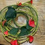 Dans une large coupe transparente, branches de saule et anthuriums travaillés en cercles.
