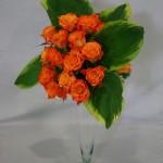Bouquet de roses oranges et hostas panachés de blanc dans une flûte en verre.