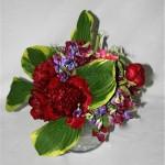Pivoines, pois de senteur et feuilles d'hostas panachés. Vase boule en verre.