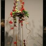 Australie. Haute et aérienne structure métallique garnie de nombreux végétaux sèchés associés à des roses et anthuriums rouges.
