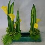 Les Callas jaunes accompagnent les lignes verticales.  Les Hypericum verts animent le bas de la composition.