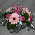 Dans une coupe en verre, germinis rose pastel et roses .