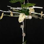 Sur un support transparent, quelques branches de Mitsumata blanchies garnies de fleurs et feuilles d'Anthuriums