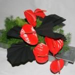 Anthuriums rouges et papier noir: contrastes de couleur et de textures.