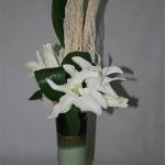 Sur un vase haut et élancé, les lys blancs ressemblent à des fleurons d'orchidée.