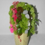 Contraste de texture entre les oeillets de poète verts,le poivre rose, les galets et les feuilles lisses du galax.