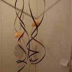 Suspension de spirales de lamelles de bois et  pivoines dans des tubes en verre. Nicole Dineur.