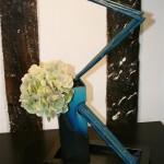 Vase en Raku et bambous teints en bleu accompagnent une tête d'hortensia.