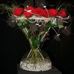 Gerbe de roses rouges habillée de feuilles squlette, graminées et baies roses.