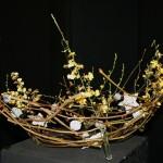 Composition de saule tortueux animéee d'orchidées Oncidium et de sujets de Noël.