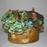 Les hortensias bleus sont mis en valeur dans une jolie boîte ovale en bois.