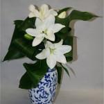 Le jeu de feuilles et le bleu du vase mettent valeur les fleurons de lilium épanouis.