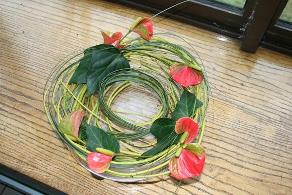 Les branches garnies d'Anthuriums et de feuilles de lierre sont ici travaillées en couronne dans une coupe en verre.