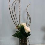 Les grandes branches de chatons de saule travaillées sont décorées d'un jeu de feuilles et de roses.
