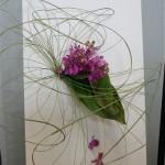 Sur un châssis entoilé, le bouquet d'orchidées Vanda est souligné par un jeu de volutes végétales.