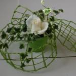 Pour les tables, un pot de ierre panaché entouré d'un ruban de vannerie garni de roses blanches.