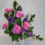Giroflées mauves et pivoines roses dessinent un bouquet asymétrique dont le coeur est souligné d'hostas.