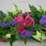 Guirlande de fleurs fraîches : vert des sedums en boutons et fougères, mauve des ageratums et roses.