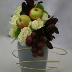 Fleurs et fruits sont travaillés en lignes et la volute de  rotin anime le vase gris.