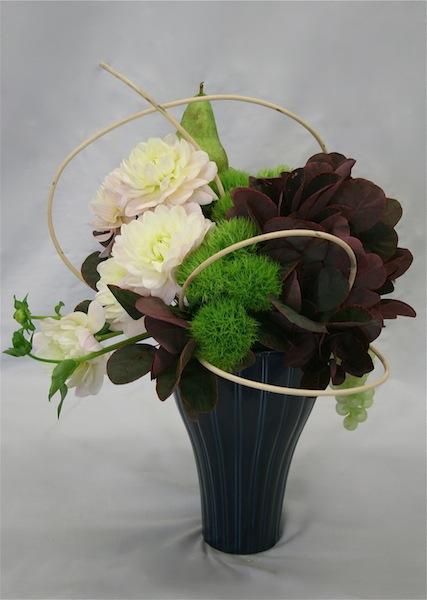 Le rotin souligne le bouquet de dahlias, oeillets de poète verts et cotinus.