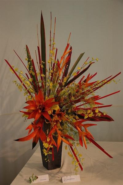 O sole mio : composition rayonnante de végétaux exotiques avec héliconia, oncidium, bromeliacée.