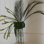 Mousson : arums et petites palmes areca sur un pied en plexiglass.