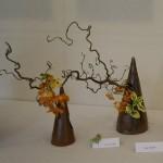 Cônes en terre cuite garnis de branches de saule tortueux, baies et fleurons d'orchidées.