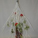 Le fagot de branches est posé à l'envers sur un vase haut et stable.