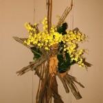 Bouquet d'accueil : orchidées oncidium sur un faisceau de stipes de fougères arborescentes.