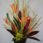 Les branches de cornouiller structurent ce bouquet exotique de fleurs d'Héliconias et feuilles de Cordyline rouge.