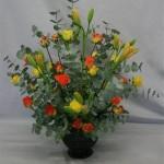 Roses de 2 couleurs et liliums jaunes en boutons habillent une masse bien disciplinée d'eucalyptus.