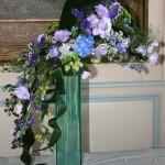 Une gerbe de fleurs variées est disposée sur le vase : lysianthus, hortensias, aconit.