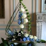 Des prêles et une tige de molucelle dessinent un bateau garni de delphiniums, callas et roses blanches .